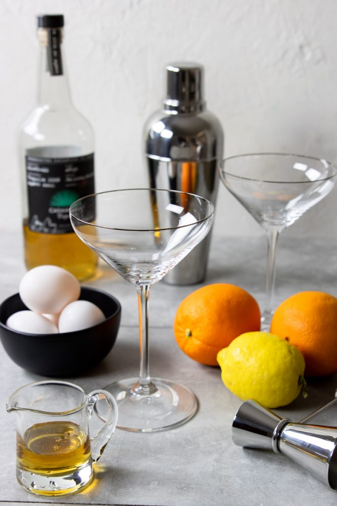 A line up of tequila sour ingredients - tequila, egg, lemon, oranges, agave syrup