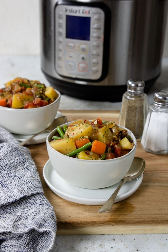 two bowls of vegetable beef soup with an instant pot in the background