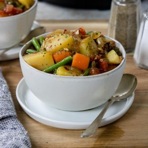A white bowl filled with vegetable beef soup