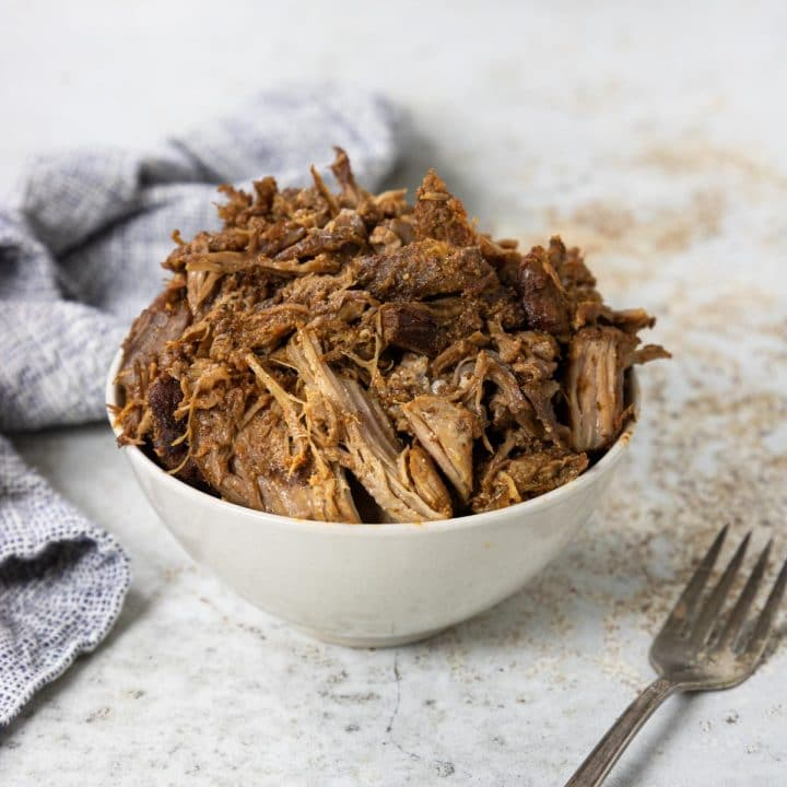 whole30 pulled pork in a bowl with a fork and napkin to the side