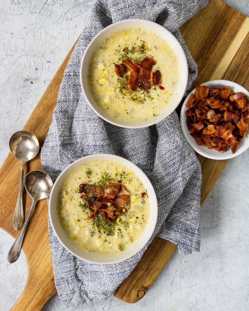 two bowls of corn chowder on a cutting board topped with bacon