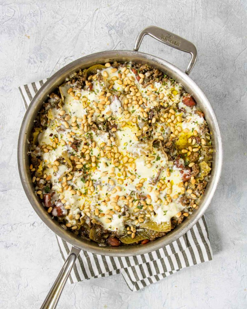 Final pesto lasagna skillet topped with pine nuts