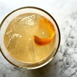 Orange Rosemary Cocktail in a glass with an orange peel