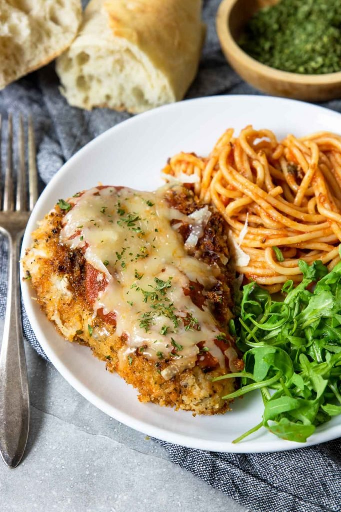 A plate with chicken parmesan, salad and spaghetti