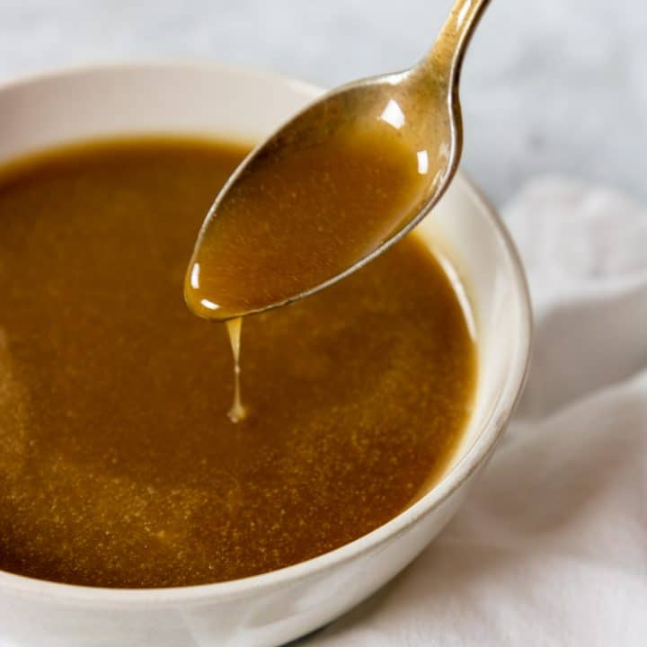 brown sugar caramel sauce in a white bowl being drizzled with a spoon