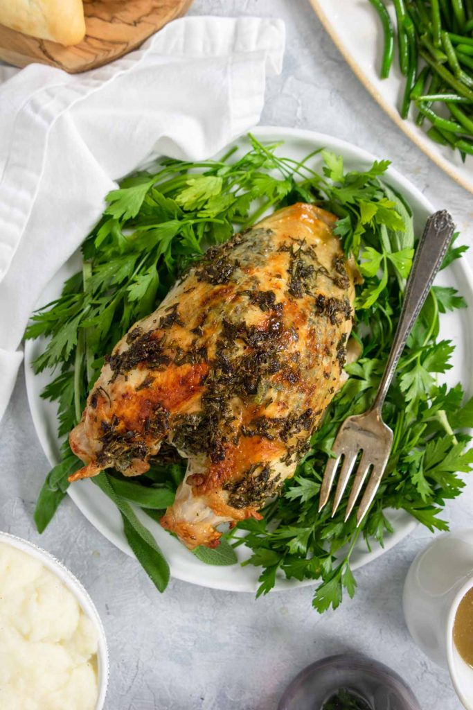 oven roasted turkey breast on a plate with herbs