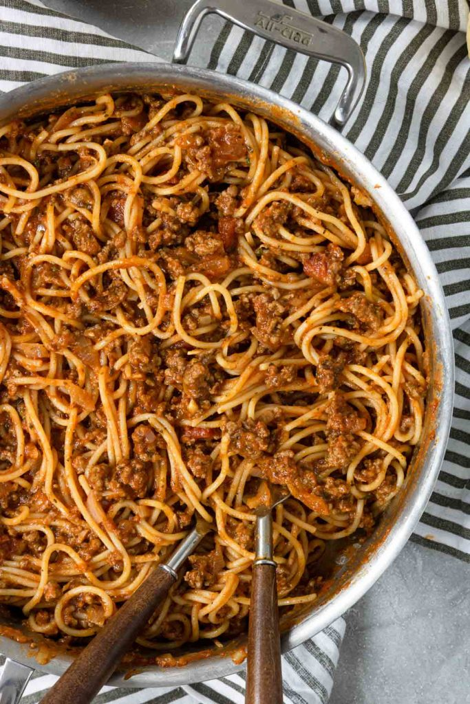 spaghetti that has been tossed with a meat sauce, in a skillet with two forks
