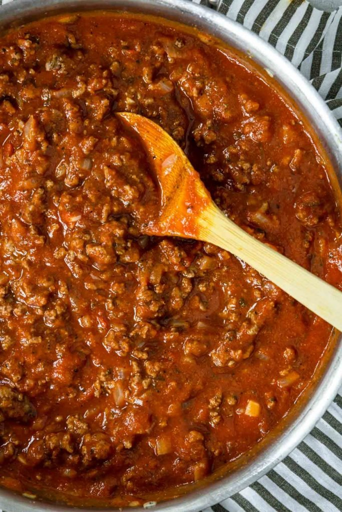 meat sauce in a skillet with a wooden spoon