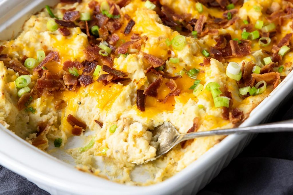 mashed potato casserole topped with cheese, green onions and bacon