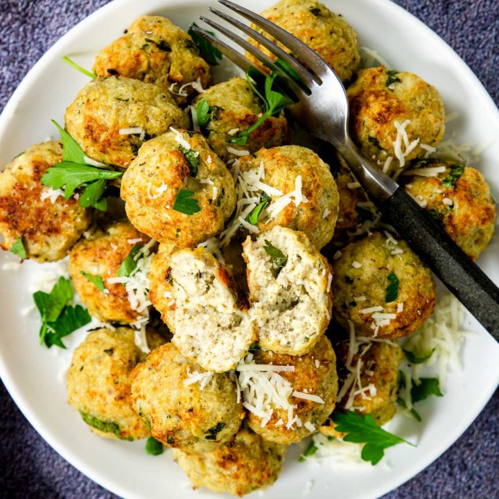 baked chicken meatballs in a pile garnished with parsley and romano cheese