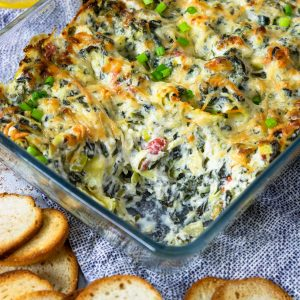 spinach artichoke dip in a baking dish with a scoop taken out