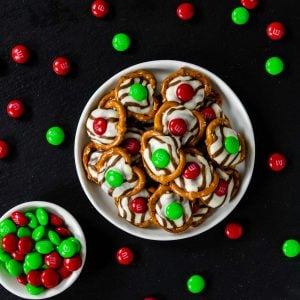 christmas hug cookies on a black slate background with holiday M&M's scattered