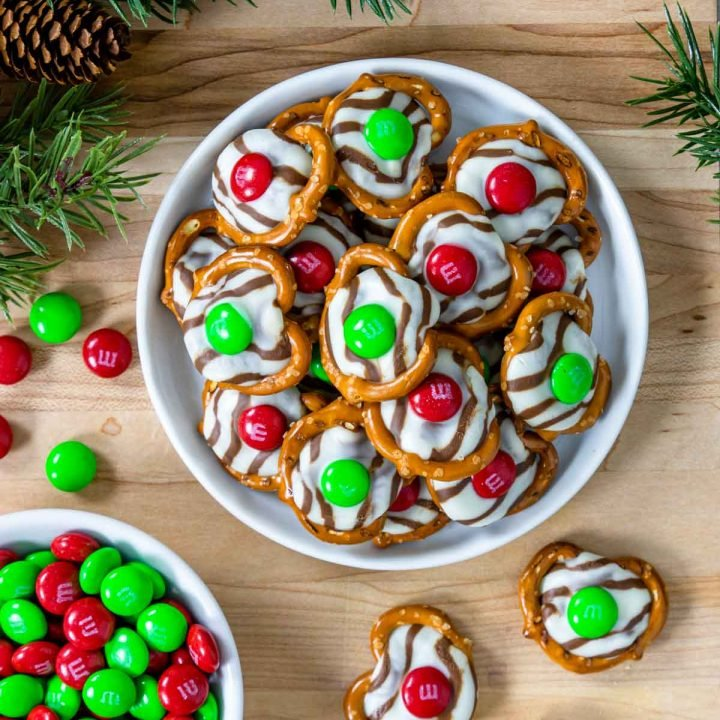 Christmas hug cookies on a plate with evergreen to the side