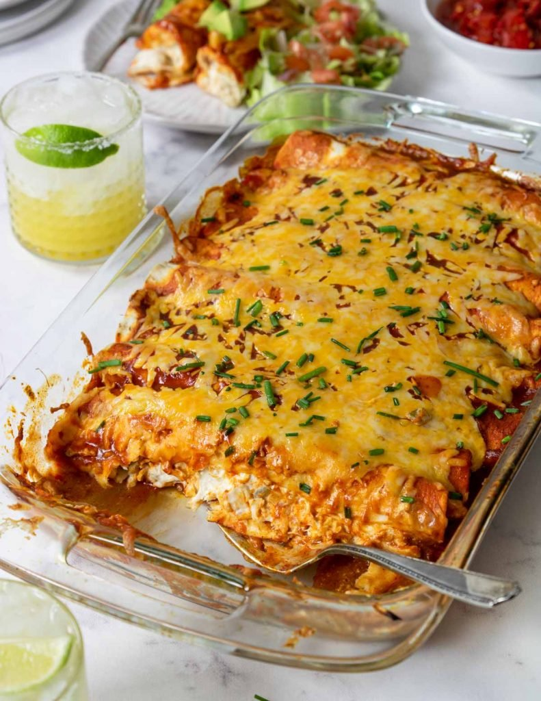 cream cheese chicken enchiladas baked in a glass casserole pan with margaritas in the background