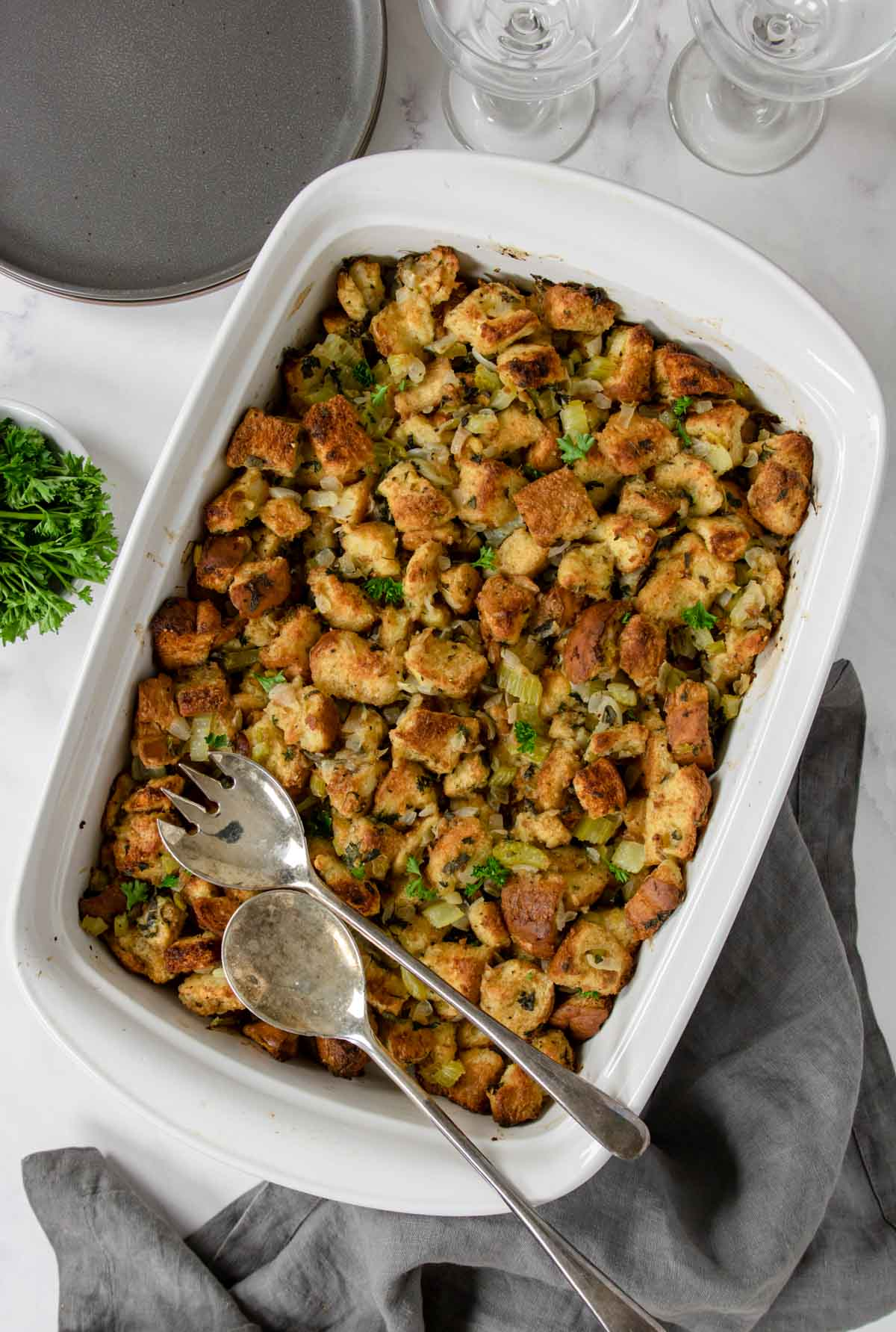 homemade bread stuffing in a baking dish with parsley garnish
