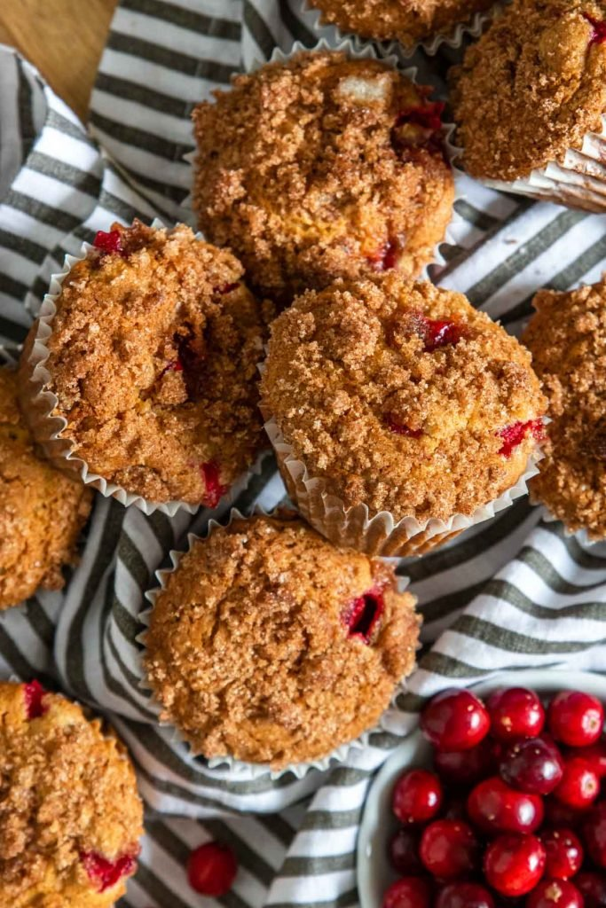 Cranberry orange muffins on a black and white napkin with fresh cranberries