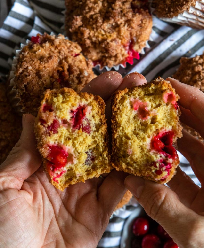 cranberry muffin broken open to show the inside with is orange with bright red cranberries