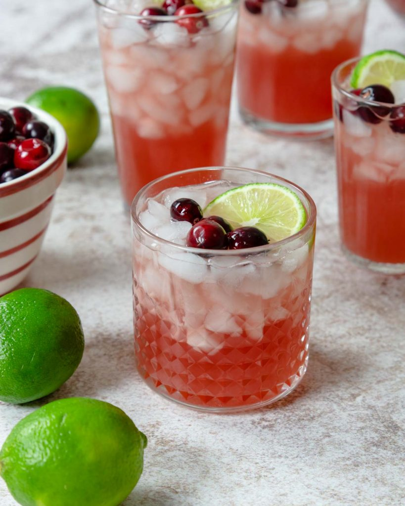 cranberry punch in a glass over ice garnished with cranberries and limes