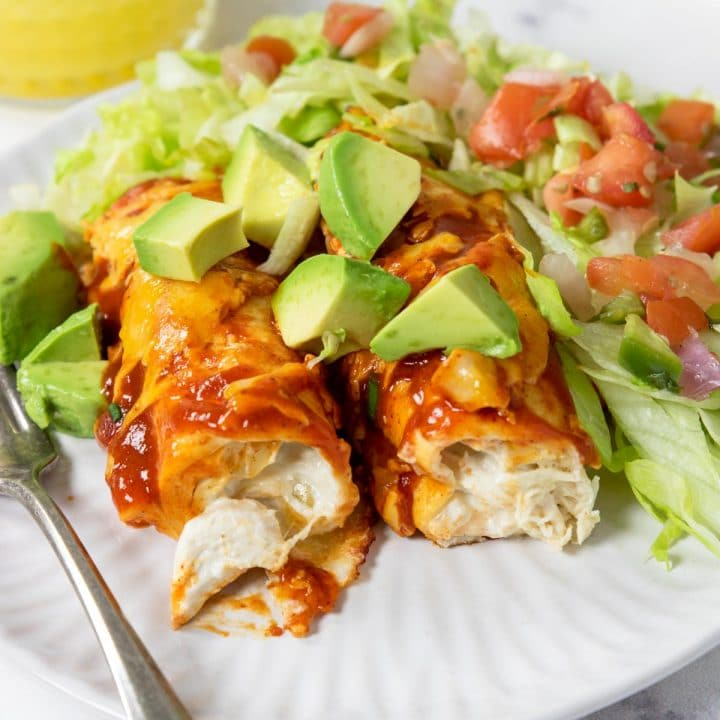cream cheese chicken enchiladas on a plate with red chili sauce, cheese, and avocados