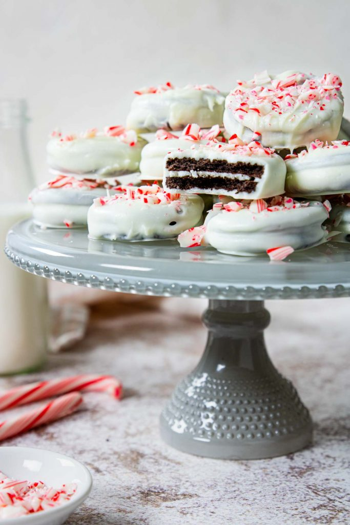 white chocolate covered oreos with crushed candy canes on top sitting on a glass cake plate