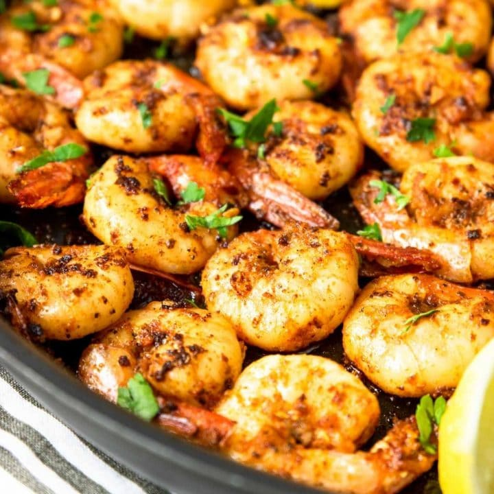 Cajun Shrimp in a skillet with lemon wedges