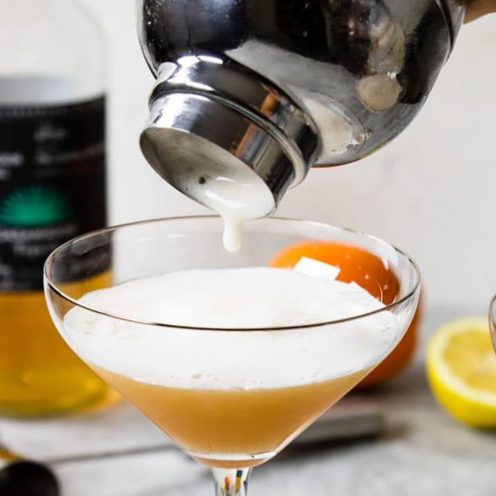 tequila sour with foam being poured into a glass