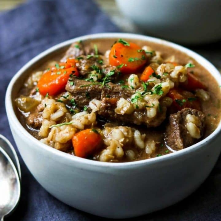 beef and barley in a white bowl with a spoon