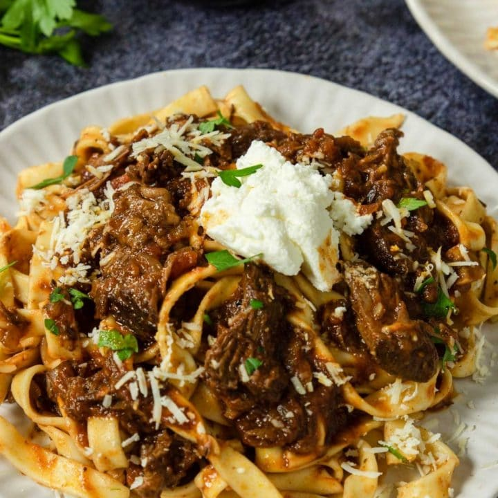 beef ragu over pasta topped with ricotta