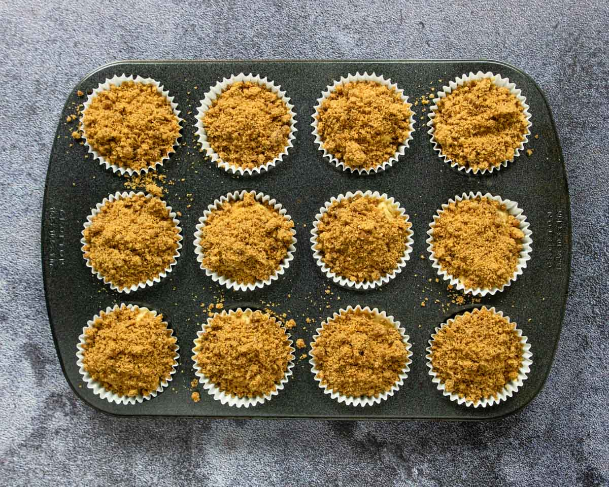 a muffin tin full of unbaked coffee cake muffins