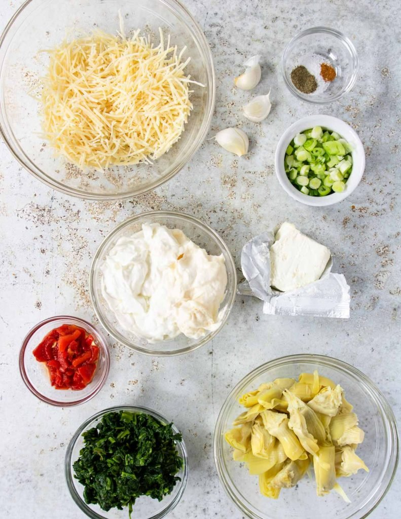 ingredients for spinach artichoke dip laid out on a table