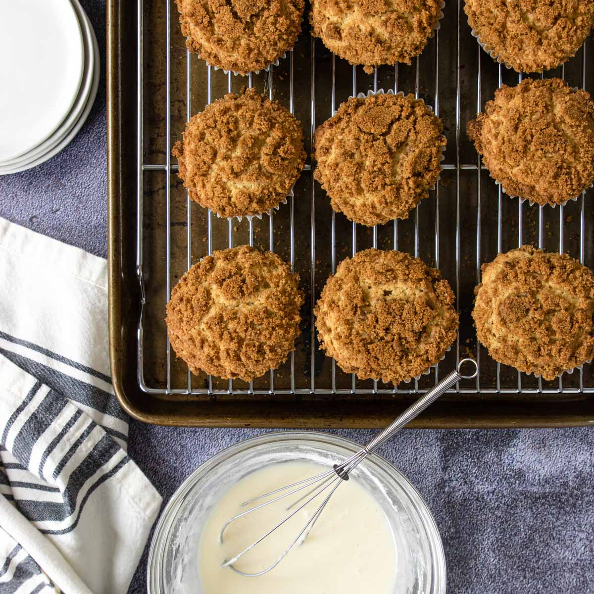baked muffins on a cooling rack with a bowl of vanilla glaze