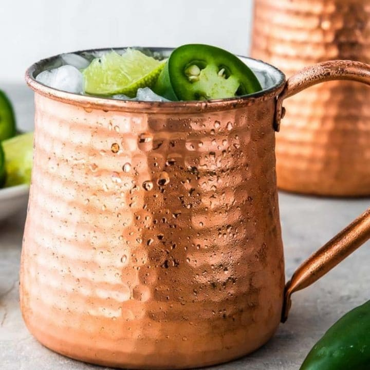 two copper mule glasses topped with jalapenos