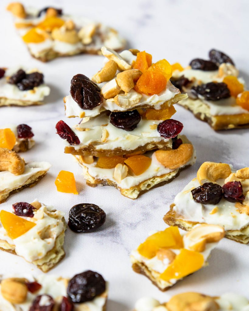 a pile of white chocolate toffee with cashews and dried fruit on top