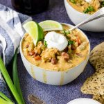 a bowl of chicken chili topped with sour cream and limes