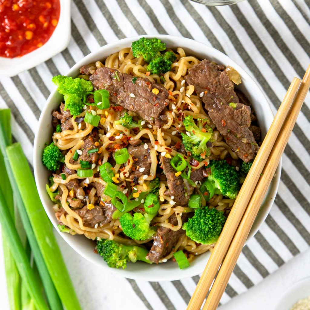 a bowl of ramen with beef and broccoli green onions and chop sticks