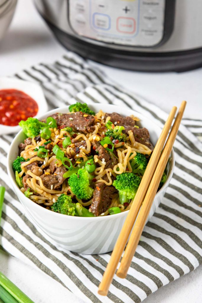 a bowl of beef ramen with broccoli and a pair of chop sticks
