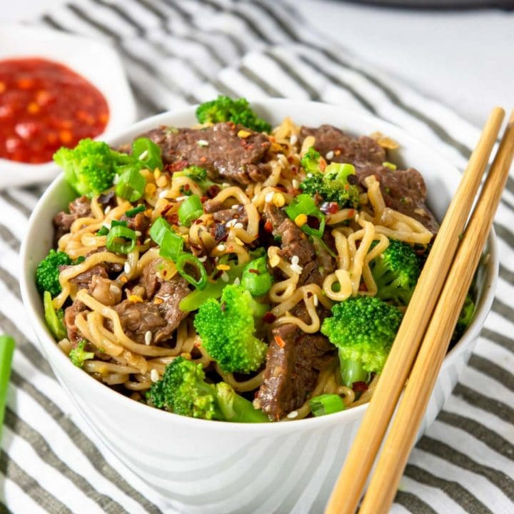 a bowl of beef and broccoli ramen with chop sticks