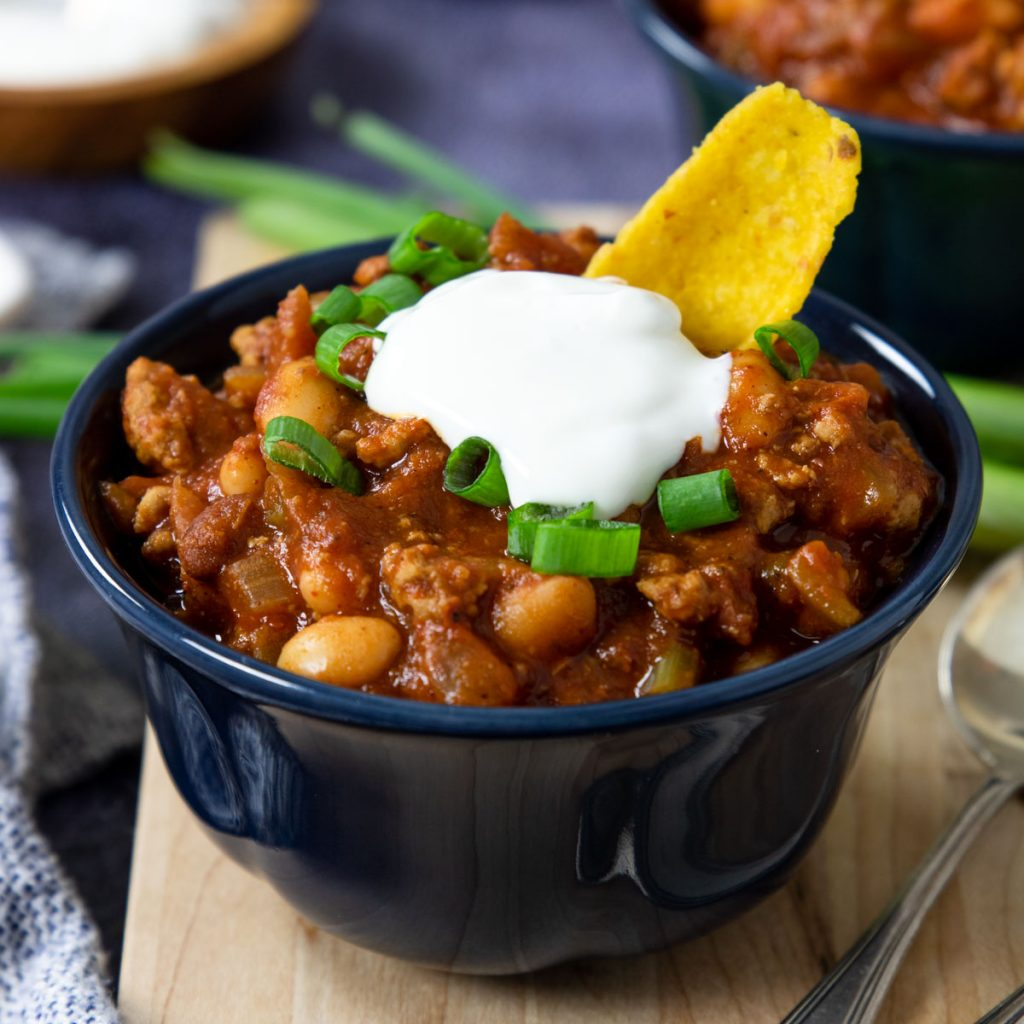 a bowls of chili with turkey topped with sour cream, fritos and green onions