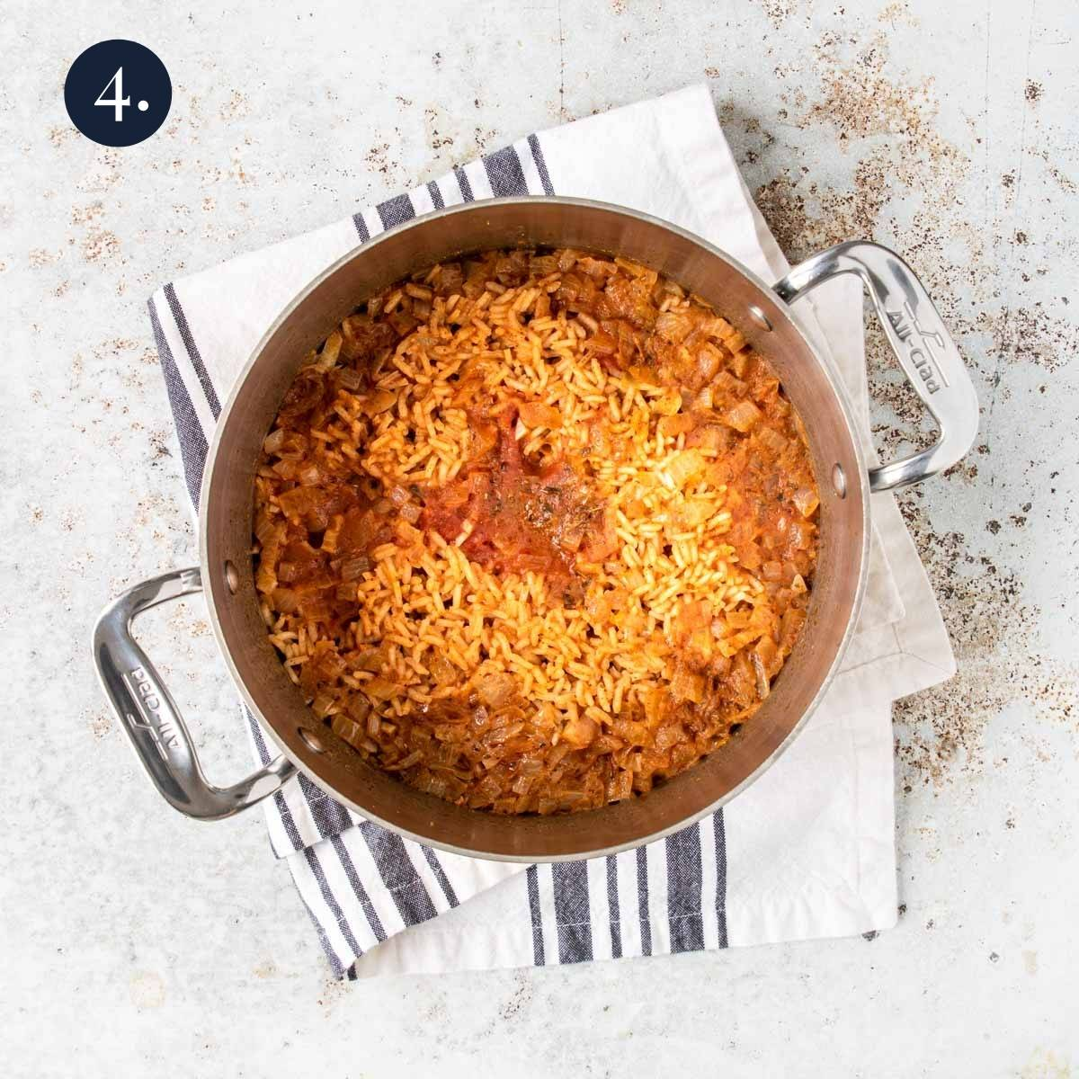 mexican rice cooked in a pot with onions and tomato sauce on top