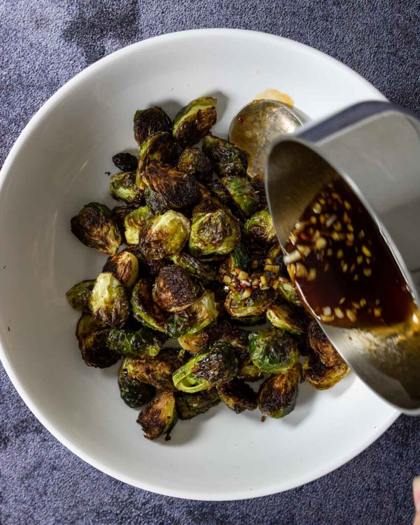 pouring ginger soy glaze over the brussels