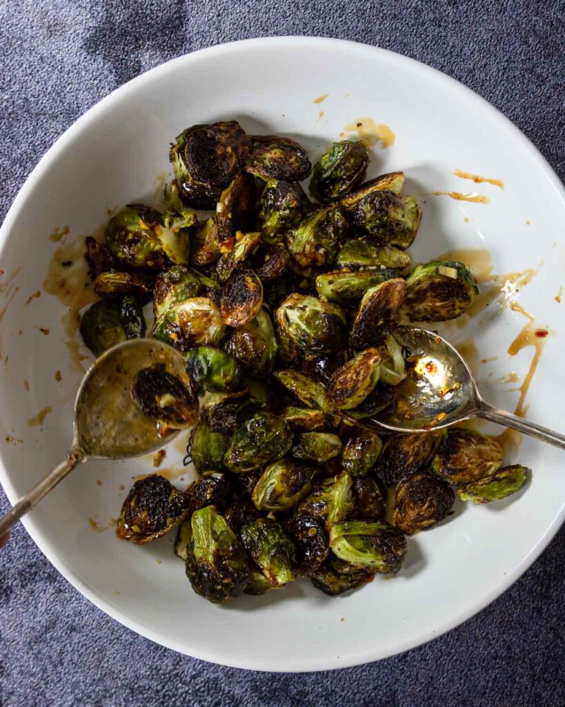 tossing roasted brussels in an Asian sauce