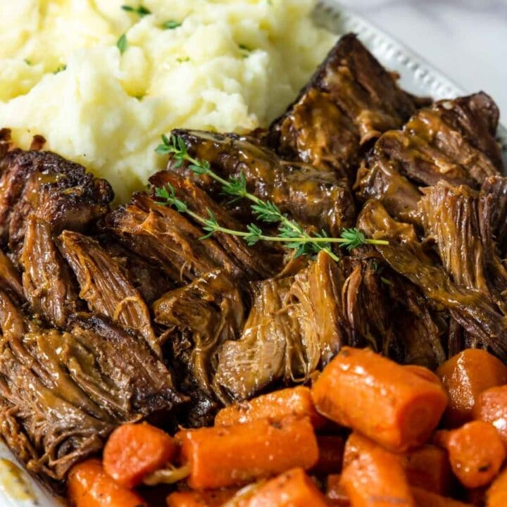 a platter of pot roast carrots and mashed potatoes