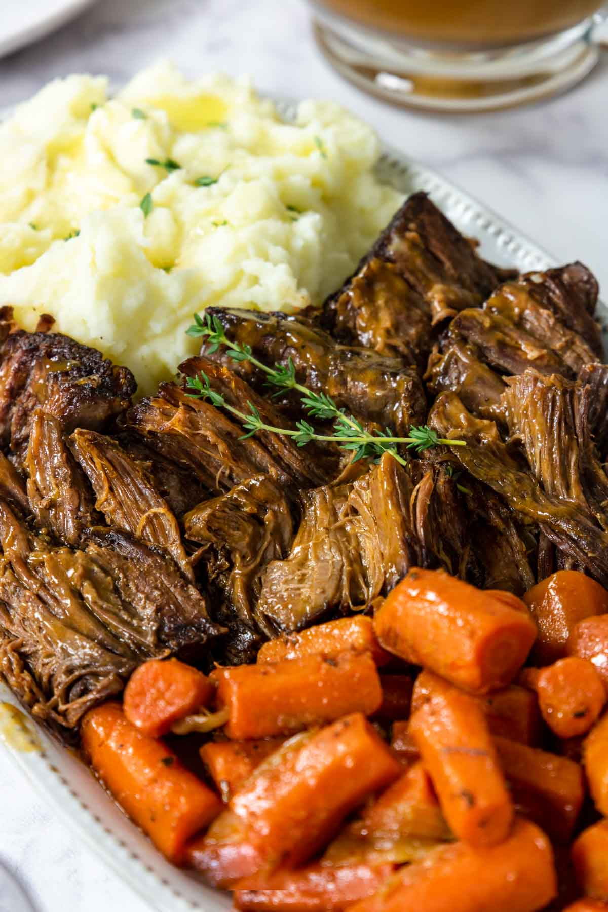 a serving plate with pot roast, mashed potatoes, and cooked carrots