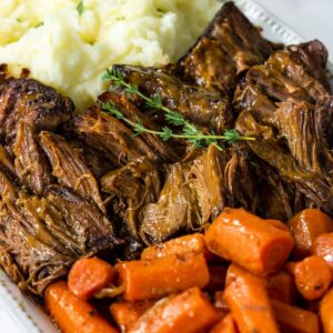 a close up of pot roast,cooked carrots and mashed potatoes