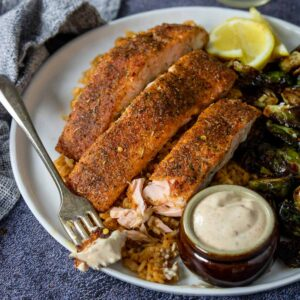 Cajun Salmon on a plate with a bite taken out and dipped in Cajun Aioli