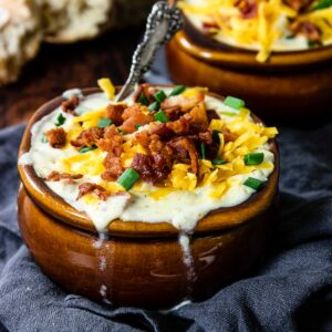 creamy red potato soup topped with bacon and cheese in a brown crock bowl