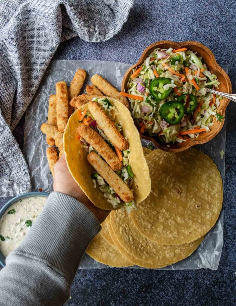corn tortilla in a hand filled with slaw and fish sticks
