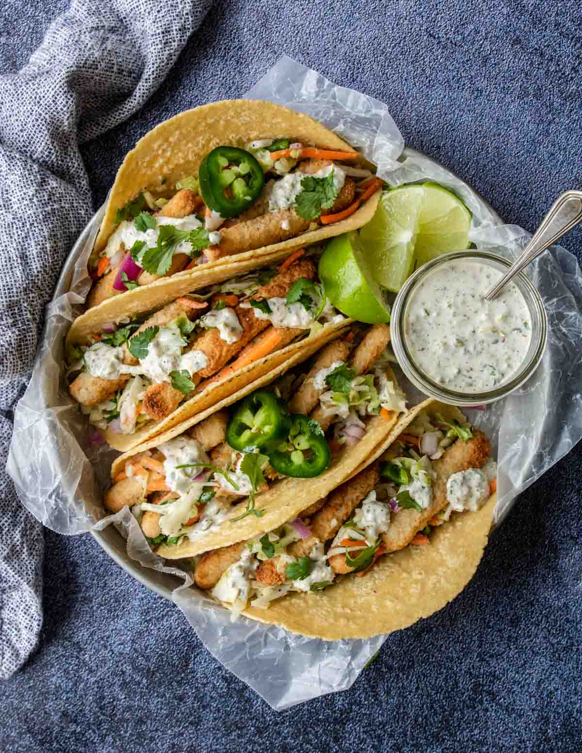 a tray full of fish stick tacos in corn tortillas