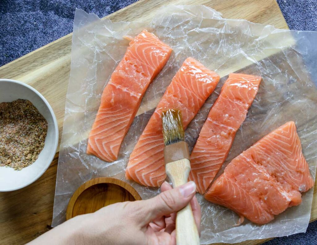 brushing salmon fillets with olive oil