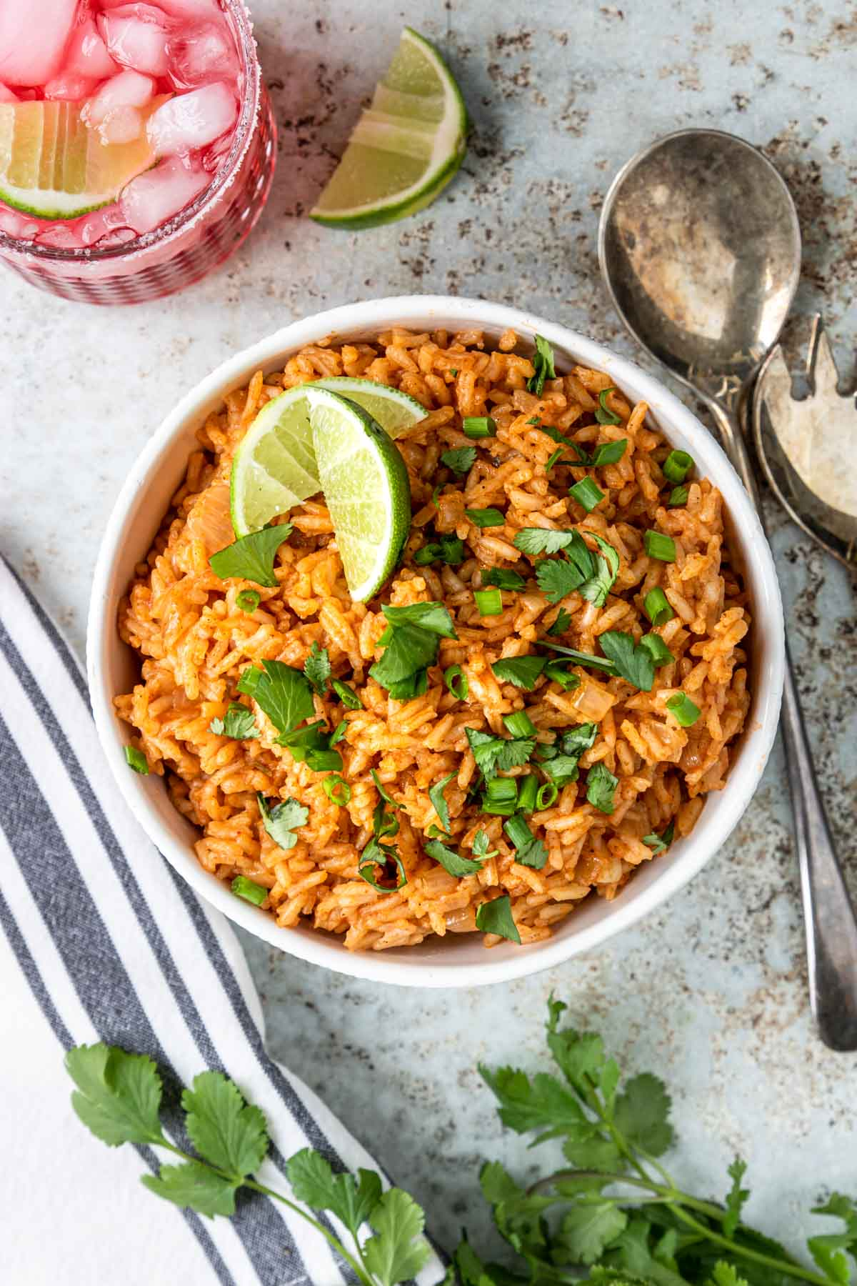 mexican rice in a bowl topped with cilantro and limes
